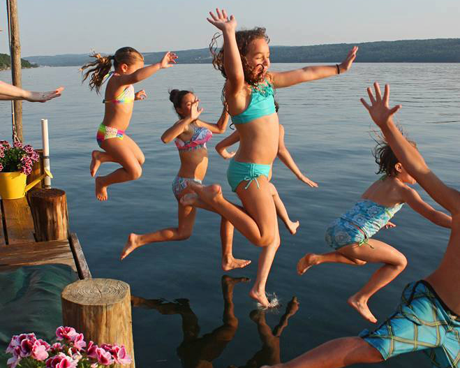 A group young children jumping into a New Hampshire lake