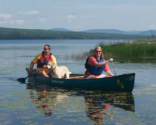 A man and a woman share a canoe with their dog
