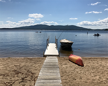 A dock with nearby boats on a New Hampshire lake