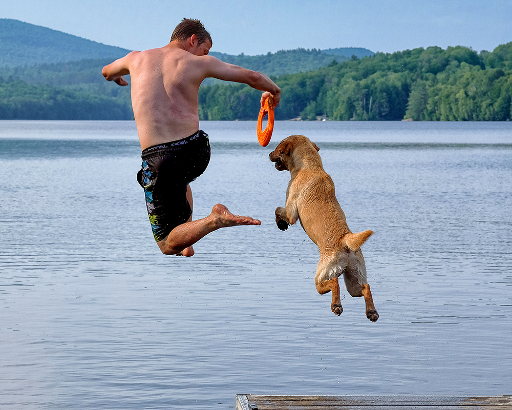 Man jumping off a dock into a New Hampshire lake with his dog