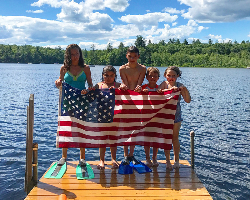 A group of kids standing on a dock with an American flag