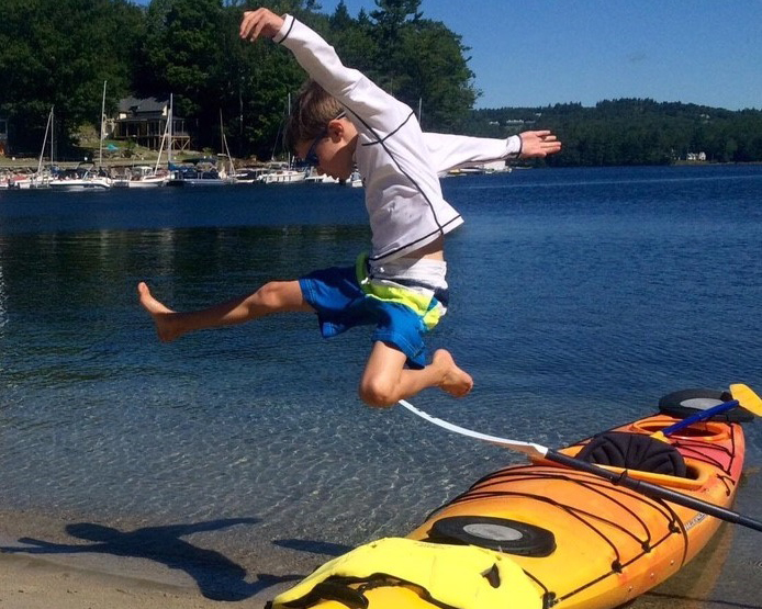 Young boy jumping in front of a New Hampshire lake