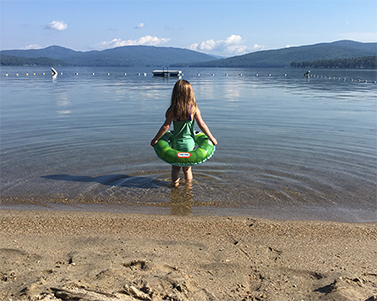A young girl stands looking out onto a New Hampshire lake