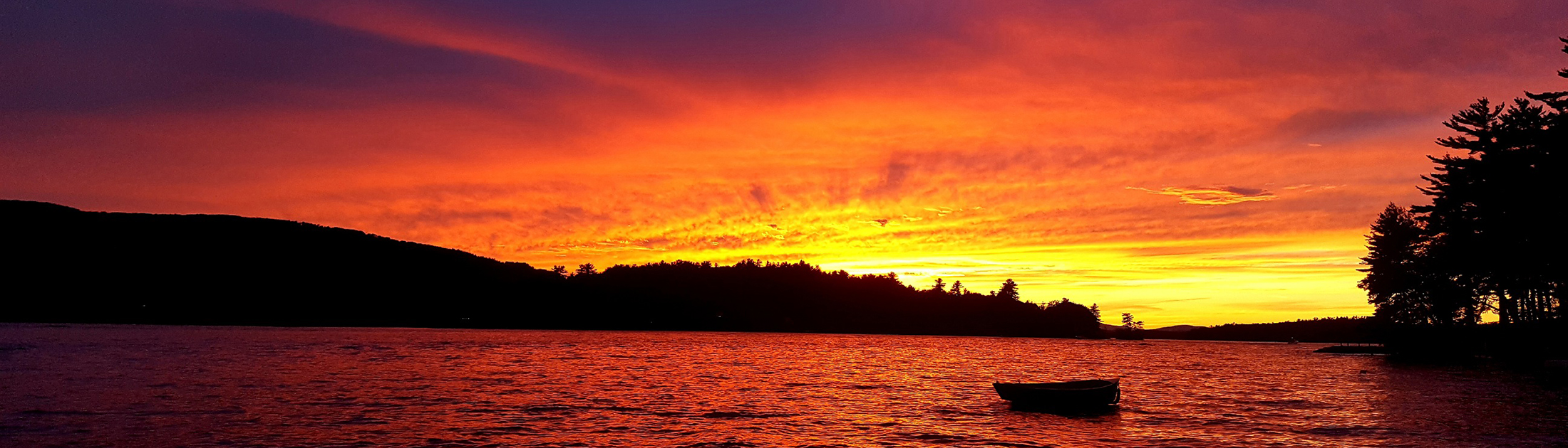 A New Hampshire lake at sunset with a boat in the foreground